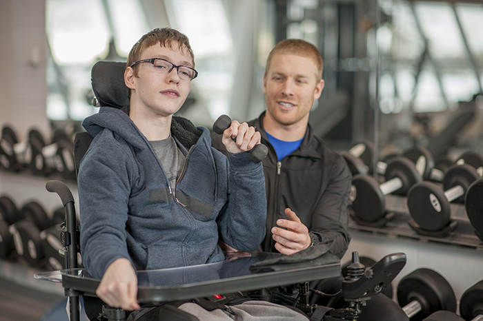 A young disabled adult doing strength exercises with a personal trainer.